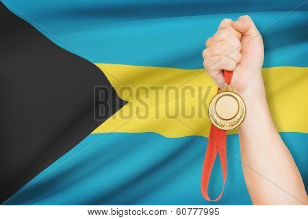 Medal In Hand With Flag On Background - Bahamas
