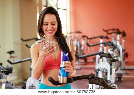 Woman on mobile, smiling in gym room