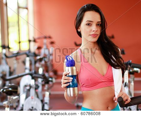 Woman on mobile, smiling in fitness gym drinking water