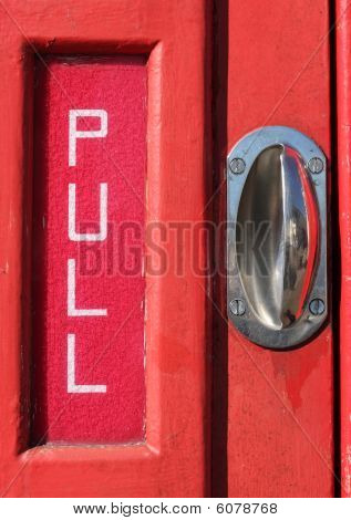 Pull Sign And Handle On A Red Telephone Kiosk Door.