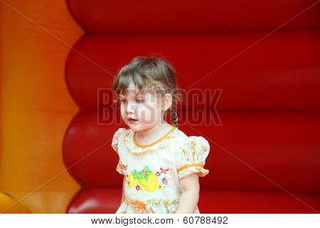 Little Beautiful Happy Girl Jumps On Red Bouncy Castle And Looks Away