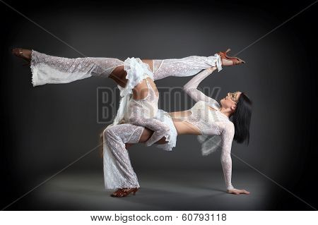 Duet of flexible slim dancers posing in studio