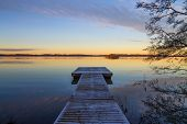 picture of jetties  - Scandinavian lake in the sunset with frozen jetty and a tree silhouette - JPG