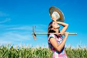 stock photo of hoe  - Tired female farmer working with hoe in corn field - JPG