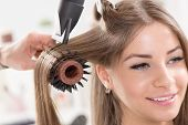 stock photo of brown-haired  - Hairdresser drying long brown hair with hair dryer and round brush - JPG