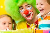 pic of clown face  - kids with clown celebrating birthday party and blowing candles on cake - JPG