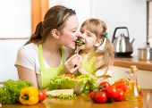 stock photo of apron  - funny mother feeding kid vegetables in kitchen - JPG