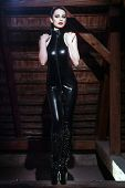 foto of sado-masochism  - Sexy young brunette dominatrix posing on timber - JPG