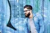 pic of graffiti  - Portrait of a male fashion model with beard and glasses standing against graffiti background - JPG