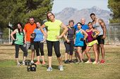 pic of boot camp  - Serious mature woman with boot camp fitness class outdoors  - JPG