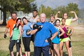 stock photo of middle class  - Serious middle aged man with weights and fitness group