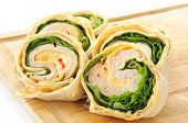 picture of sandwich wrap  - A turkey and cheese wrap sandwich sliced on a cutting board - JPG
