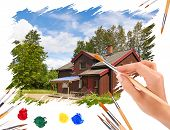 Hand With A Brush Painting Of House With Blue Sky