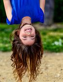 stock photo of upside  - beautiful child hanging upside laughing with greenery in the background - JPG