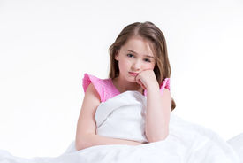 image of nighties  - Adorable thoughtful little girl in pink nightie awake and sitting on the bed  - JPG