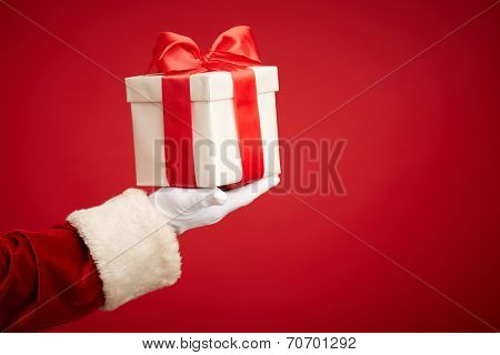 Santa Claus gloved hand with giftbox in isolation