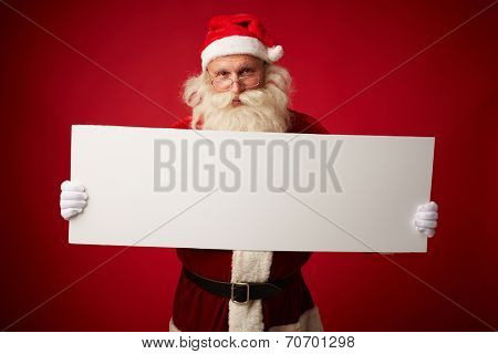 Portrait of Santa with blank paper looking at camera