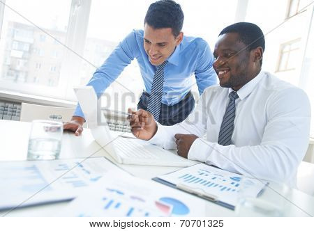 African-american businessman pointing at laptop screen while explaining project to his colleague