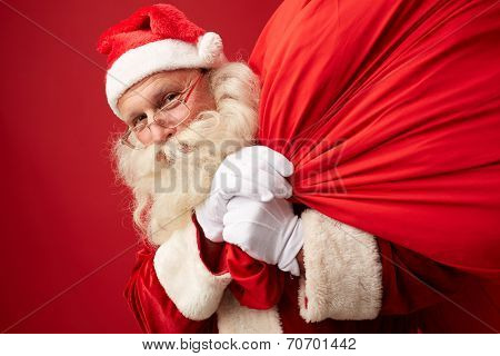 Portrait of Santa Claus with huge sack looking at camera