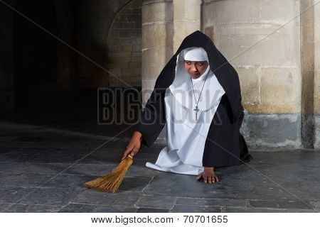 Nun sweeping the floor of a medieval abbey with a hand brush