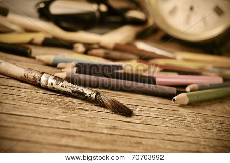 a stained brush, colored pencils of different colors, a pair of eyeglasses and an old clock on a table of a studio, with a retro effect