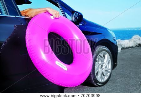 young man holding a swim ring outside of the window of a car