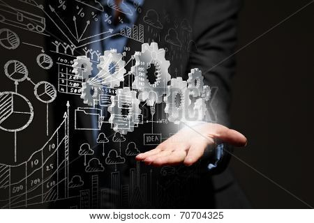 Close up of business person hand holding gears