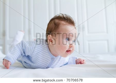 Smiling Baby Tummy Time In A White Nursery