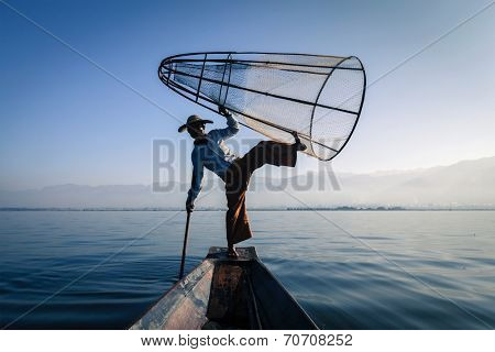 Myanmar travel attraction landmark - Traditional Burmese fisherman silhouette balancing with fishing net at Inle lake in Myanmar famous for their distinctive one legged rowing style, view from boat