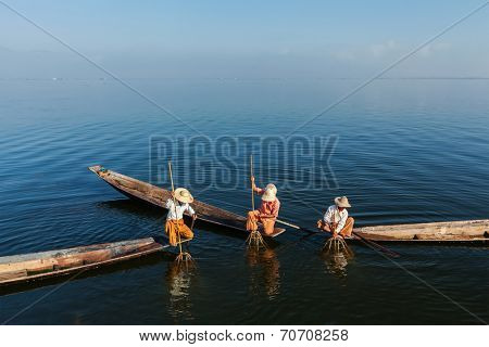Myanmar travel attraction landmark -  three traditional Burmese fishermen fishing on boats atInle lake in Myanmar famous for their distinctive one legged rowing style