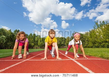 Smiling children on bending knees ready to run