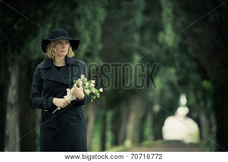 Portrait of a woman at cemetery holding flowers