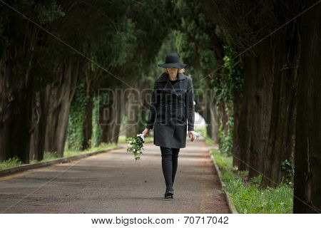 Woman walking in a cemetery holding flowers