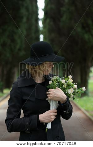 Close-up of a sad woman at cemetery holding flowers