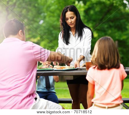 family of four eating at barbecue cookout