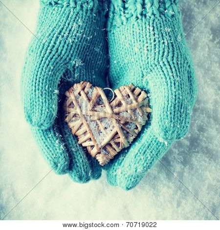 Woman hands in light teal knitted mittens are holding a beautiful heart in a snow background. Love and St. Valentine concept. Instagram effect.