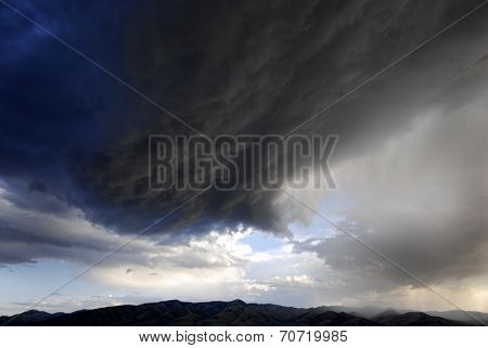 Landscape of storm clouds passing over mountain range
