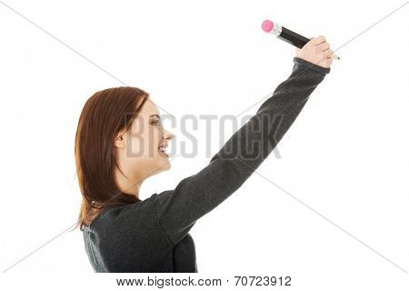 Woman writing with pencill on abstract screen