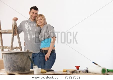 Happy casual caucasian couple standing front of painted white wall. Home renovation, new home, indoors. ladder and bucket, brush. Hugging. Smiling, looking at camera.