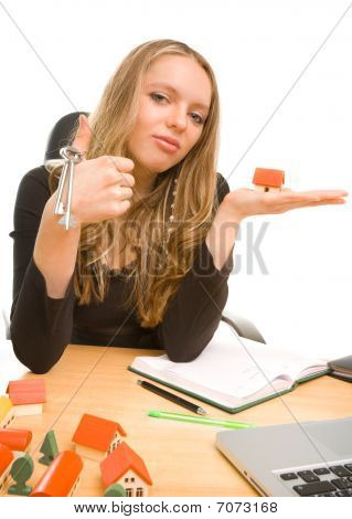 Businesswoman With Keys And Toy House At Office
