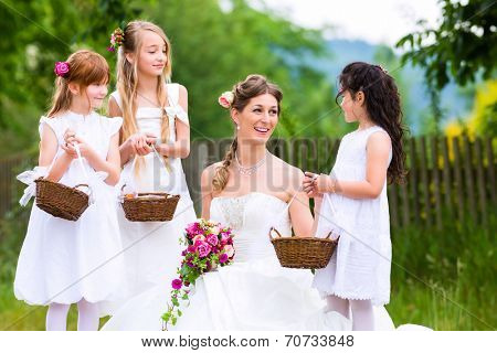 Wedding bride with flower children or bridesmaid outside at garden