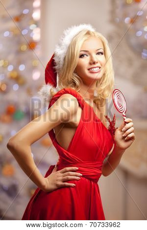 Young beautiful smiling santa woman near the Christmas tree with bunny. Fashionable luxury  girl celebrating New Year.