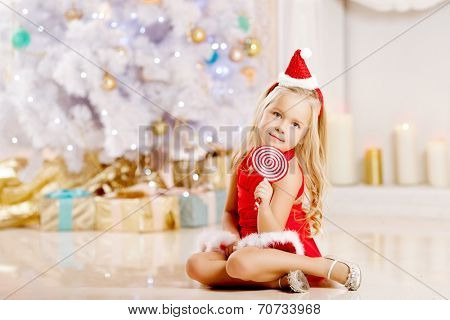 Beauty little Santa girl near the Christmas tree.  Happy girl  celebrates christmas.