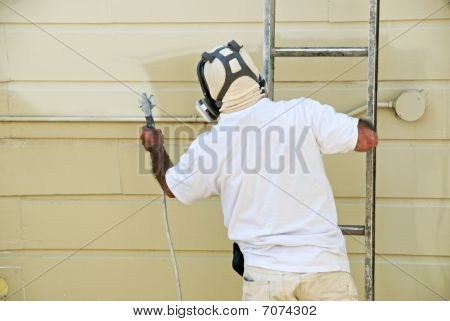 Worker With Paint Gun On Ladder
