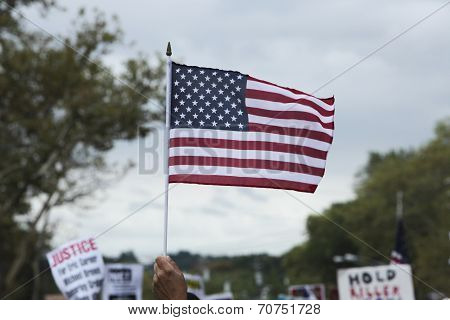US flag with sky & signs in the background