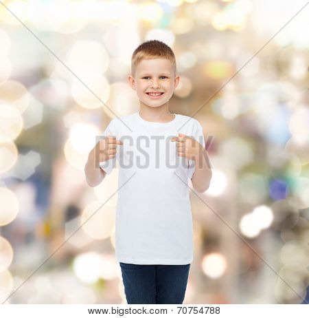 advertising, gesture, people and childhood concept - smiling boy in white blank t-shirt pointing fingers himself over holidays background