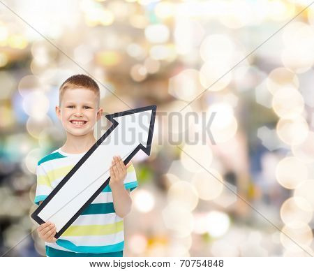 advertising, direction, holidays and childhood concept - smiling little boy with white blank arrow pointing up over sparkling background