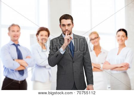 business, office, gesture and people concept - group of smiling businessmen making hush sign in office