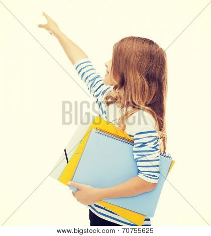 advertisement and education concept - smiling little student girl with notebook and folders pointing to something