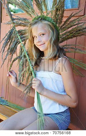 Girl Weaves A Wreath Of Grass